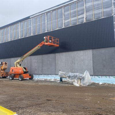 Metal panels starting to go up around the gym. The plastic above will eventually all be windows.
